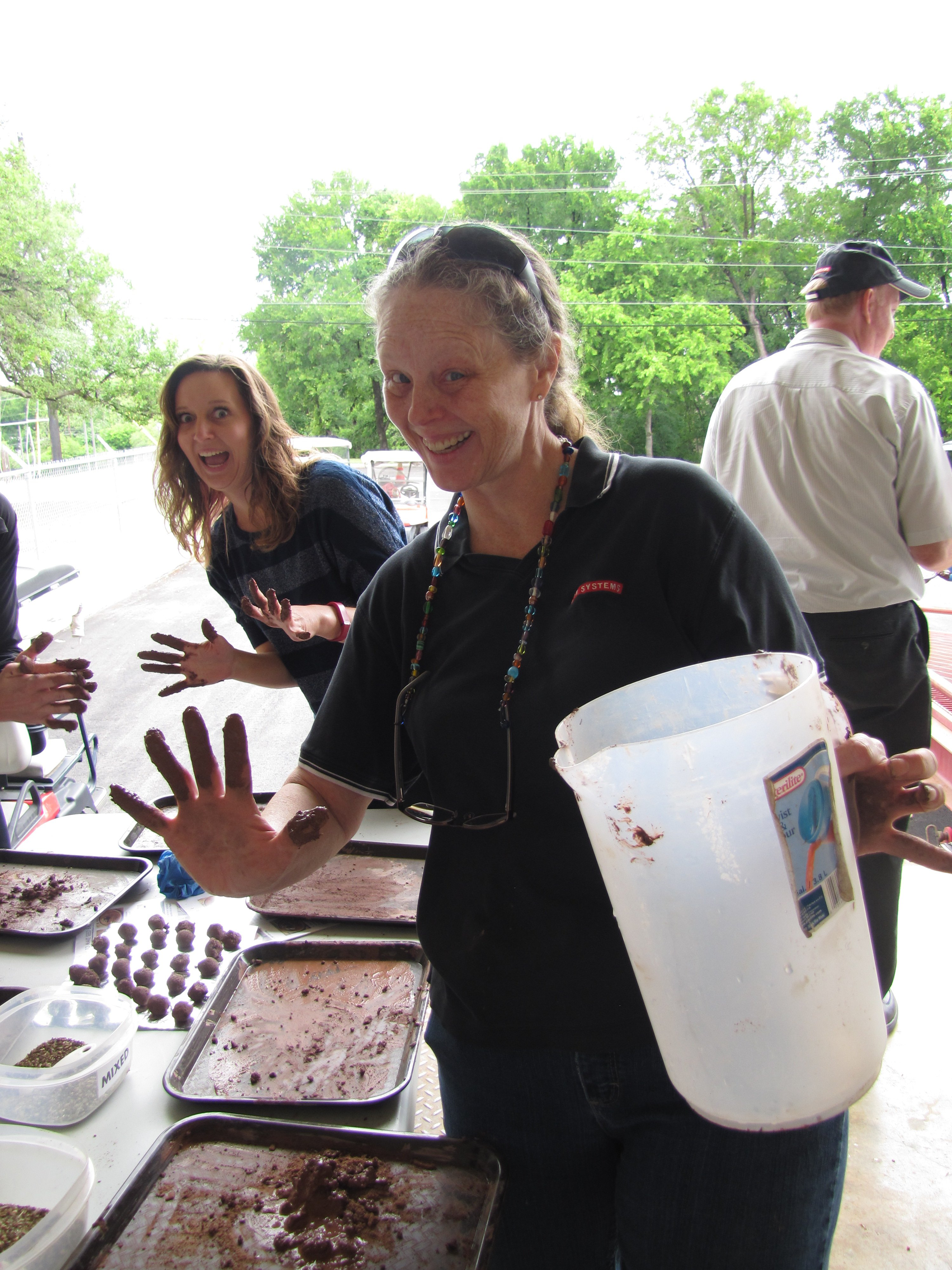 BAE Systems employees enjoy getting their hands dirty to make seedballs to be distributed across the campus in Austin, Texas.