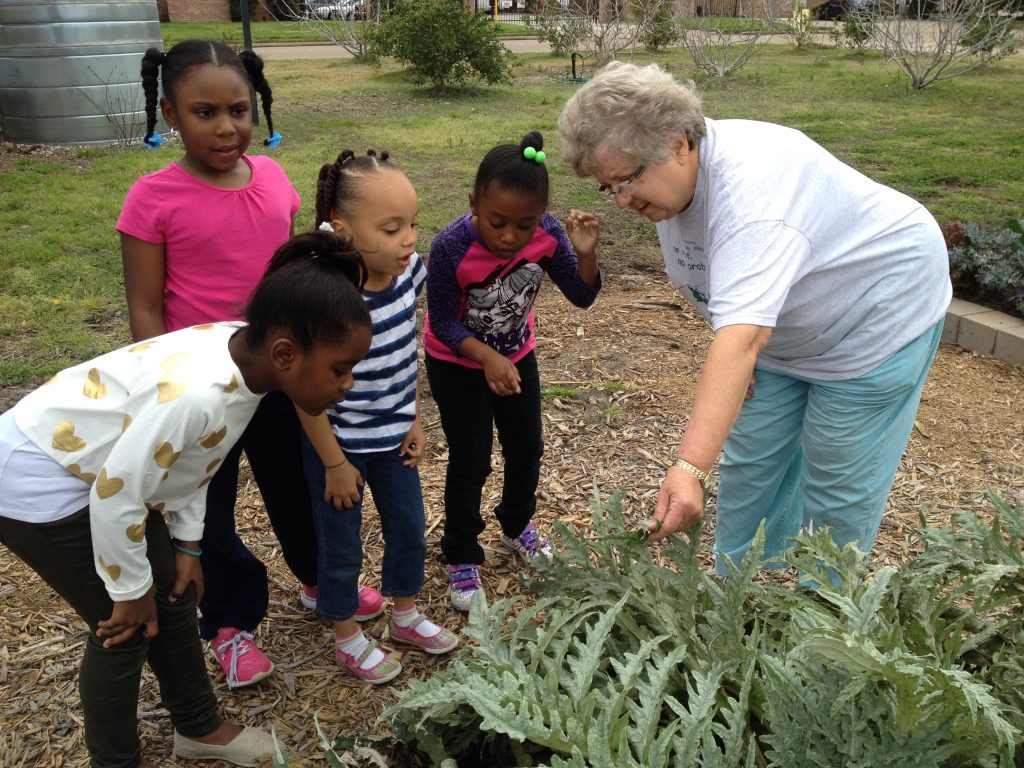 A WCG member teaching students in the garden